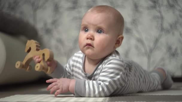 Kis gyönyörű szőke baba csíkos pizsamában játszik a földön fából készült lóval, és megpróbálja megenni.