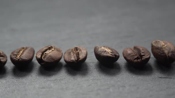 Coffee beans lie in row on stone. The camera slowly fly left over coffee.