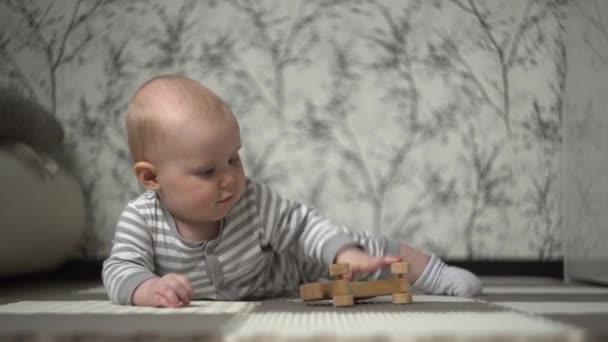 Malé krásné blond dítě v pruhovaném pyžamu hraje na podlaze s dřevěným koněm a snaží se ho sníst