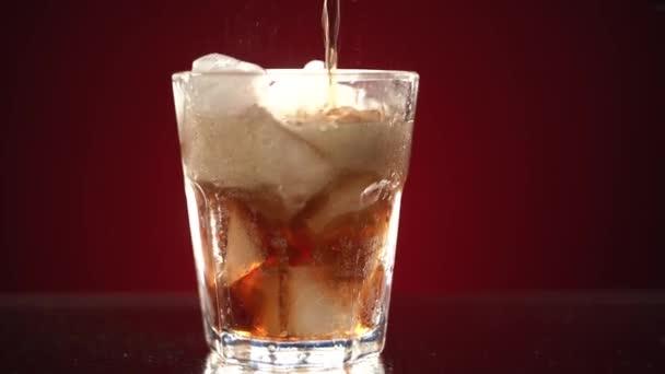 Ein durchsichtiges Glas mit einem Bund Eis ist mit Coca-Cola gefüllt. Ein Glas steht auf einem feuchten Tisch mit Wassertropfen auf rotem Hintergrund. Limonade