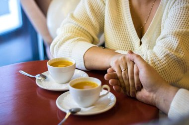 man and woman hold hands, close up of couple's arms on red wooden table in restaurant with two white cups with tea on it. date in cafe