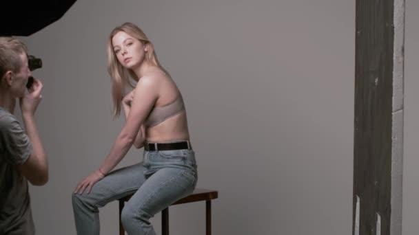 Backstage von männlichen Fotografen, die Fotos von sexy kaukasischen Frau posieren