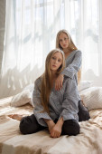 pretty twin sisters in jeans and striped shirts with long hair sitting on bed