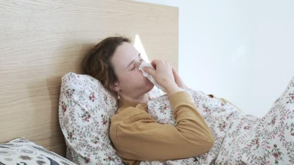 Kranke Mädchen niesen, pusten, Nase mit Seidenpapier wischen. Frau hustet im Bett