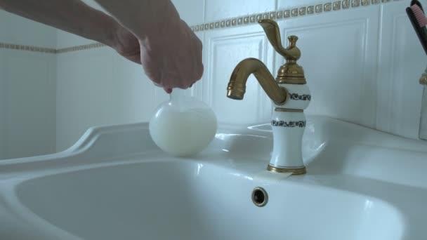 nerozpoznatelný běloch myje ruce mýdlem v umyvadle v bílé koupelně