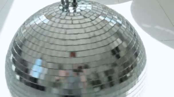 rotating vintage disco ball on floor in beam of sun with bright reflection spots