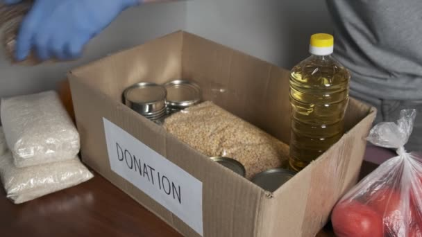 Ehrenamtliche tragen Schutzhandschuhe und legen Lebensmittel in Spendenbox