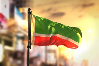 Chechen Republic Flag Against City Blurred Background At Sunrise