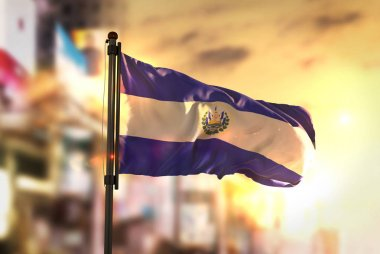 El Salvador Flag Against City Blurred Background At Sunrise Back
