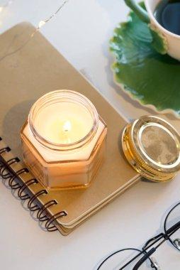 Bir fincan çay ve beyaz bir masanın üzerindeki defterde aromatik mumlar.