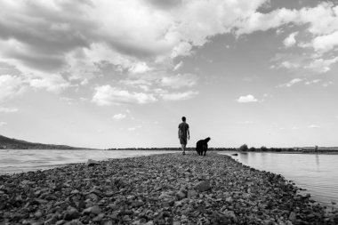 Man and his dog walking on the sandy path across the lake on a b