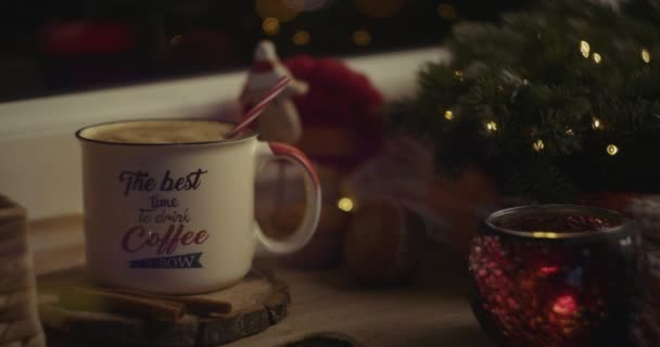 Female hand inserting a straw in a beverage in a cozy Christmas atmosphere.