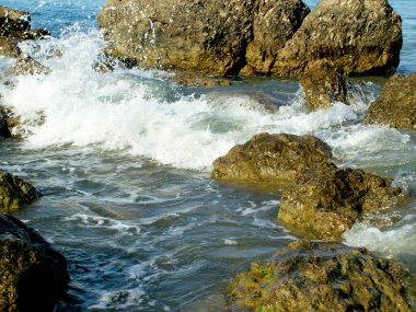 bubbling waves on a rocky pebble sea shore in the afternoon in summer