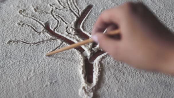 Samičí ruka maluje strom života prstem na mouku.Kreslení na mouku, strom života, kreslení stromu, kreslení na mouku, umění, kreslení, výtvarník, malování, zábava