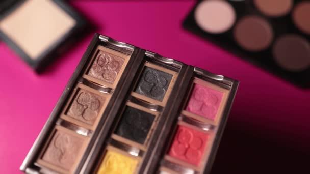 Štětec sbírat barevné oči stíny pro make-up na růžovém pozadí. Make-up kartáč, tón, tvář, krása, kůže, kontury, profesionální, krása, vzhled, oči stín