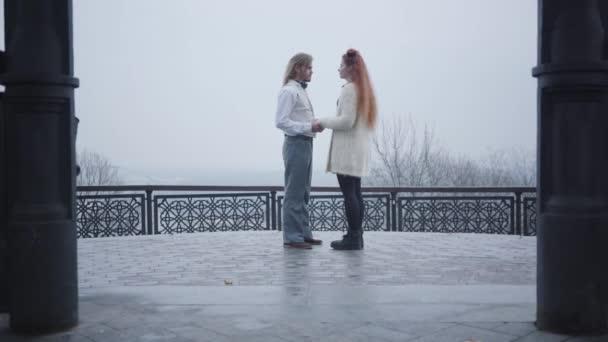 Dlouhý záběr stylového muže v retro tričku a vestě, jak se ohýbá na koleni a žádá svou přítelkyni o ruku. Mladý běloch dává snubní prsten ženě a objímá svou budoucí ženu.