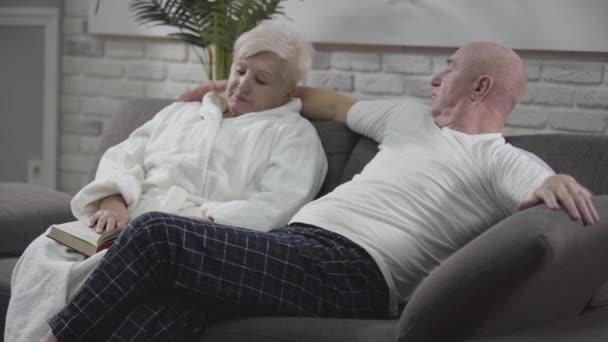 Pohled na staršího bělocha sedícího na gauči, objímajícího svou ženu, mluvícího a gestikulujícího. Starší zamilovaní pár stráví spolu klidný večer. Věčná láska, sounáležitost, štěstí.