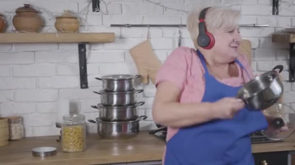 Happy smiling senior Caucasian woman in headphones dancing at the kitchen holding saucepan. Energetic dance of mature lady . Cheerful retiree enjoying life after retirement.