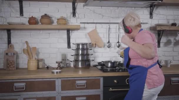 Energetic dance of mature Caucasian woman in headphones cooking at the kitchen. Funny senior lady pouring pasta into saucepan, singing and dancing. Cheerful retiree enjoying life after retirement.