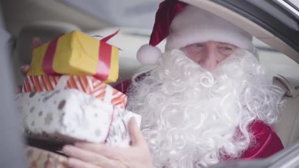 Szakállas Mikulás ajándékdobozokat ad a felismerhetetlen gyereknek a kocsi ablakából. Az öreg Télapó a kocsiban ül a hátsó ülésen. Karácsony, ünnep, ajándék koncepció
