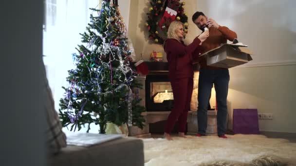 Mladá běloška věší ozdoby na vánoční stromeček. Její veselý manžel vzal králičí uši čelenku a nasadil ji na manželčinu hlavu. Šťastná rodina zdobení domu na Silvestra.