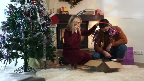 Pozitivní běloch muž a žena vybírá vánoční dekorace v krabici jako manžel vytahuje ukulele. Veselý přítelkyně a přítel baví jako zdobení domu na Silvestra.