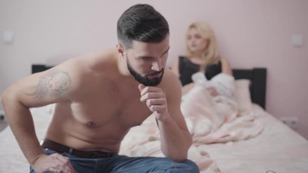 Upset Caucasian man sitting on bed, looking back at wife or girlfriend. Sad blurred woman lying at the background. Intimate problems. marriage, aging.