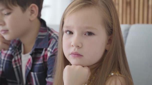 Detailní portrét smutné bělošky s hnědýma očima, dívající se do kamery a pryč, zatímco rozmazlený chlapec hladí její hlavu na pozadí. Kamarád uklidňuje rozrušenou dámu. Přátelství, první láska, péče.