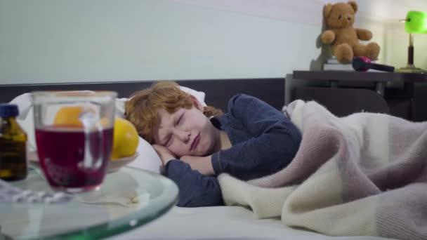 Porträt eines weinenden kaukasischen Jungen, der vor Tabletten, Orangen und heißem Tee auf dem Tisch im Bett liegt. Verärgertes krankes Rotschopfkind, das am Wochenende zu Hause bleibt. Krankheit, Gesundheit, Kindheit.