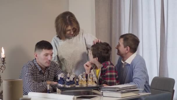 Four Caucasian people of different ages looking at camera and smiling. Happy little boy, his father and grandparents spending evening indoors playing chess. Joy, leisure, lifestyle.