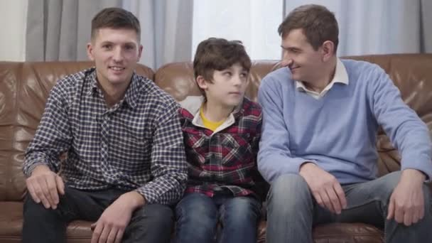 Camera approaching to little Caucasian boy sitting on couch and hugging his father and grandfather. Happy boy posing with family indoors. Lifestyle, leisure, portrait.