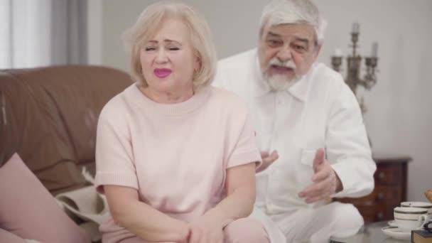 Portrét podrážděné staré bělošky, jak mluví s manželem. Starší žena si stěžuje manželce, soustřeďuje se na seniora, omlouvá se v pozadí. Životní styl, konflikt, hádky.