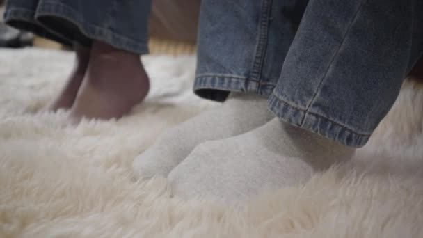 Side view close-up of male feet in jeans and socks and female legs at the background. Young man and woman resting indoors without shoes. Lifestyle, relaxation, leisure.