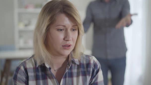 Detailní záběr vystresované bělošské mladé ženy, která poslouchá muže křičícího v pozadí. Žena v depresi se doma hádá s manželem. Životní styl, manželské problémy, rozvod, rozchod.