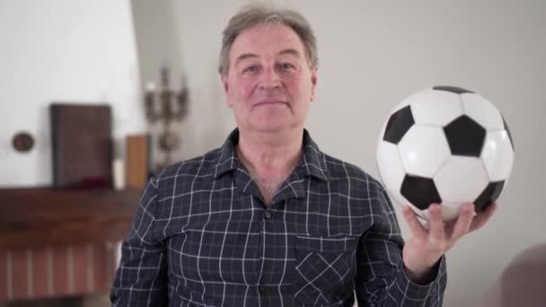 Egy magabiztos fehér férfi portréja, aki focilabdával pózol. Az idős ember imádja a focit, a kamerát nézi és mosolyog. Aktív idősek, életmód, sport, vitalitás.