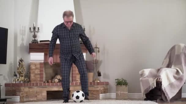 Weitschuss des glücklichen aktiven kaukasischen Rentners, der mit dem Fußballball in der Halle trainiert. Positiv gesunder älterer Mann, der zu Hause Fußball spielt und den Schuss abgibt. Lifestyle, Hobby, Sport.