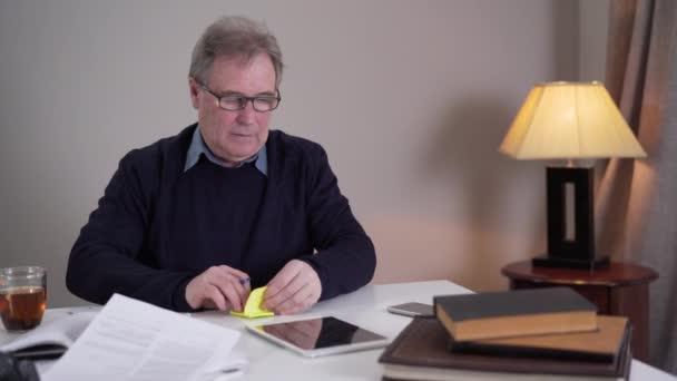 Starší běloch píše poznámky a strká je do předmětů na stole. Dospělý důchodce v brýlích bojující s nemocemi a stárnutím. Životní styl, problém, Alzheimerova choroba.