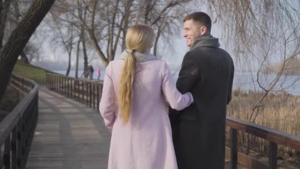 Pohled zezadu na dospělého bělocha v elegantních kabátech v parku. Pozitivní manželský pár si užívá slunečného podzimního dne venku. Štěstí, životní styl, víkendy, volný čas.