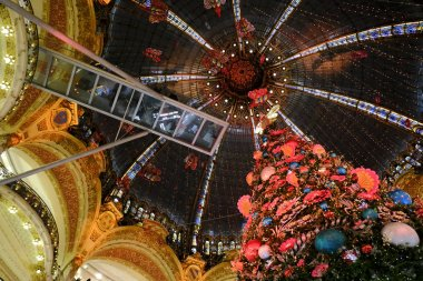 A giant christmas tree stands in the center of the Galeries Lafayette department store in Paris, France on Dec. 18, 2019.