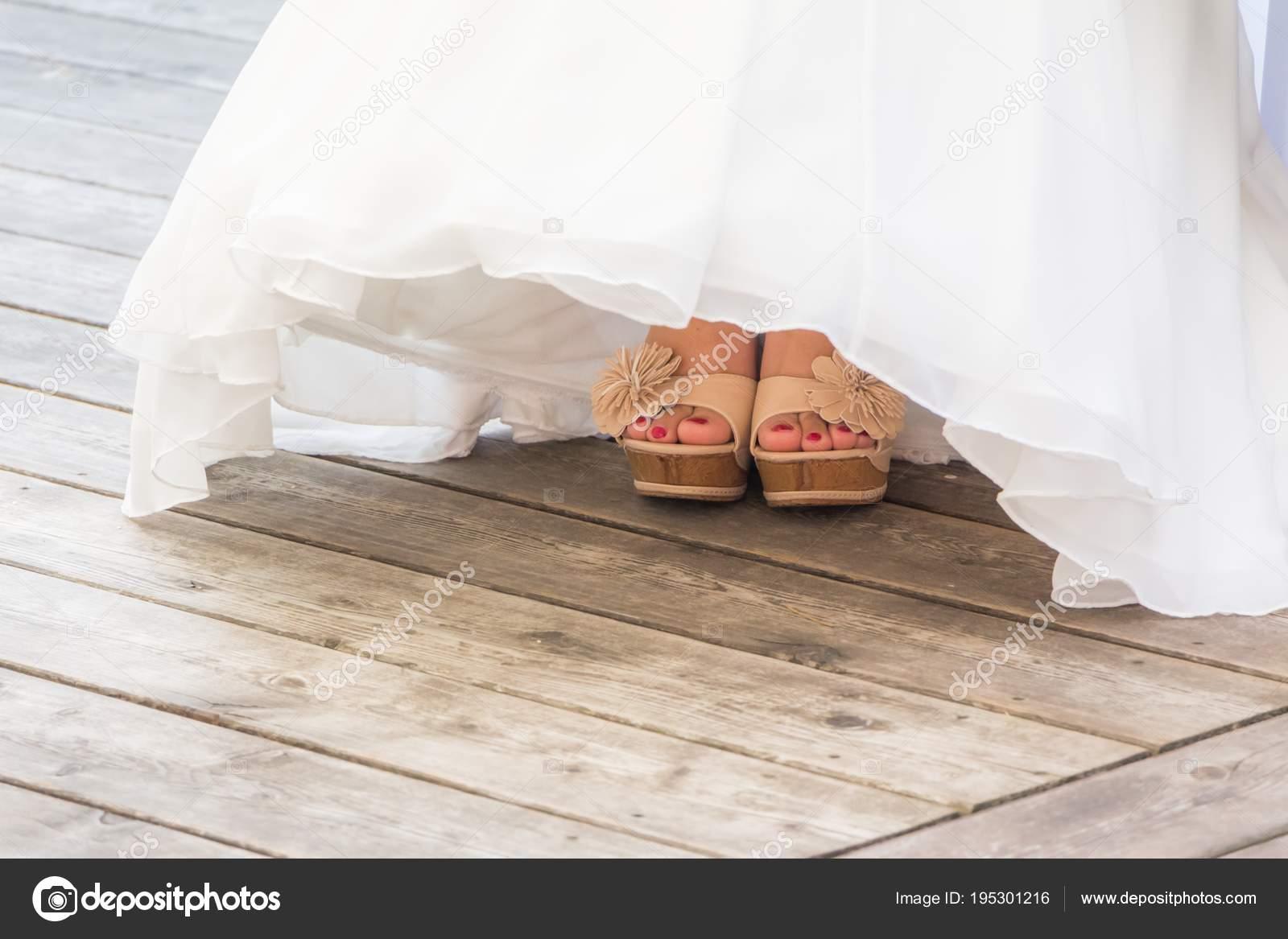 bd75ffcad39 A mulher está usando o vestido de noiva de estilo de vida de luxo. A garota  está mostrando seus pés com sapatos brancos e verniz das unhas-de-rosa.