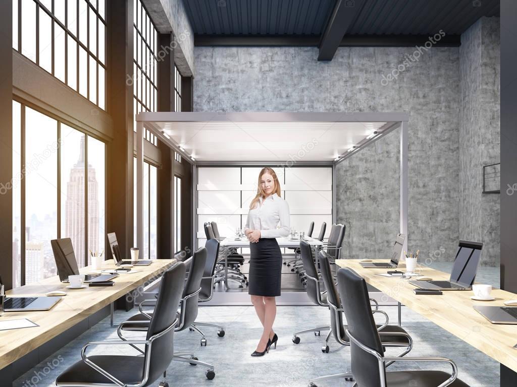 Femme debout dans le bureau ouvert avec salle de conseil de verre à