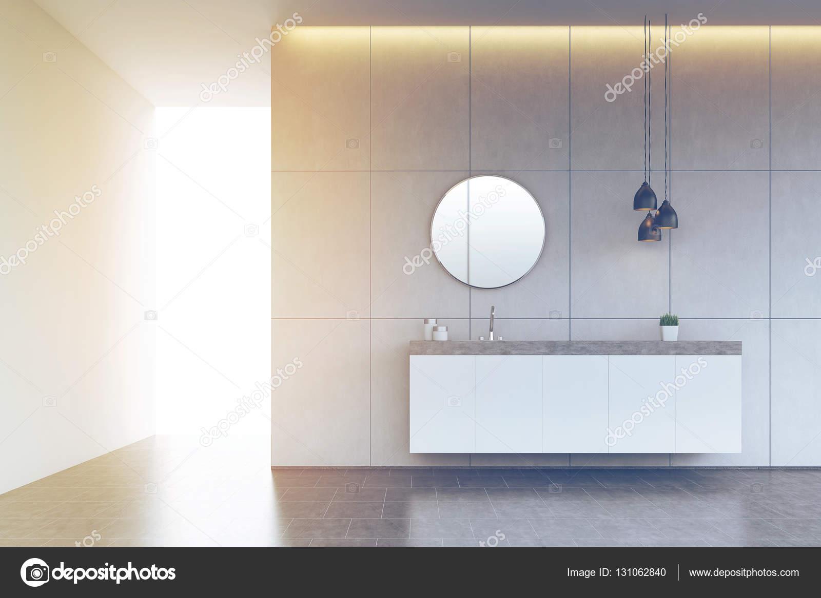 Lavandino del bagno con lo specchio rotondo su parete piastrellata