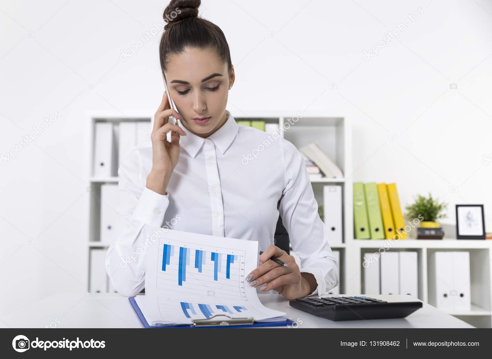 bca2b88f0aca Γυναίκα σε μια λευκή μπλούζα στο κινητό της σε ένα γραφείο που βλέπουν μια– εικόνα  αρχείου