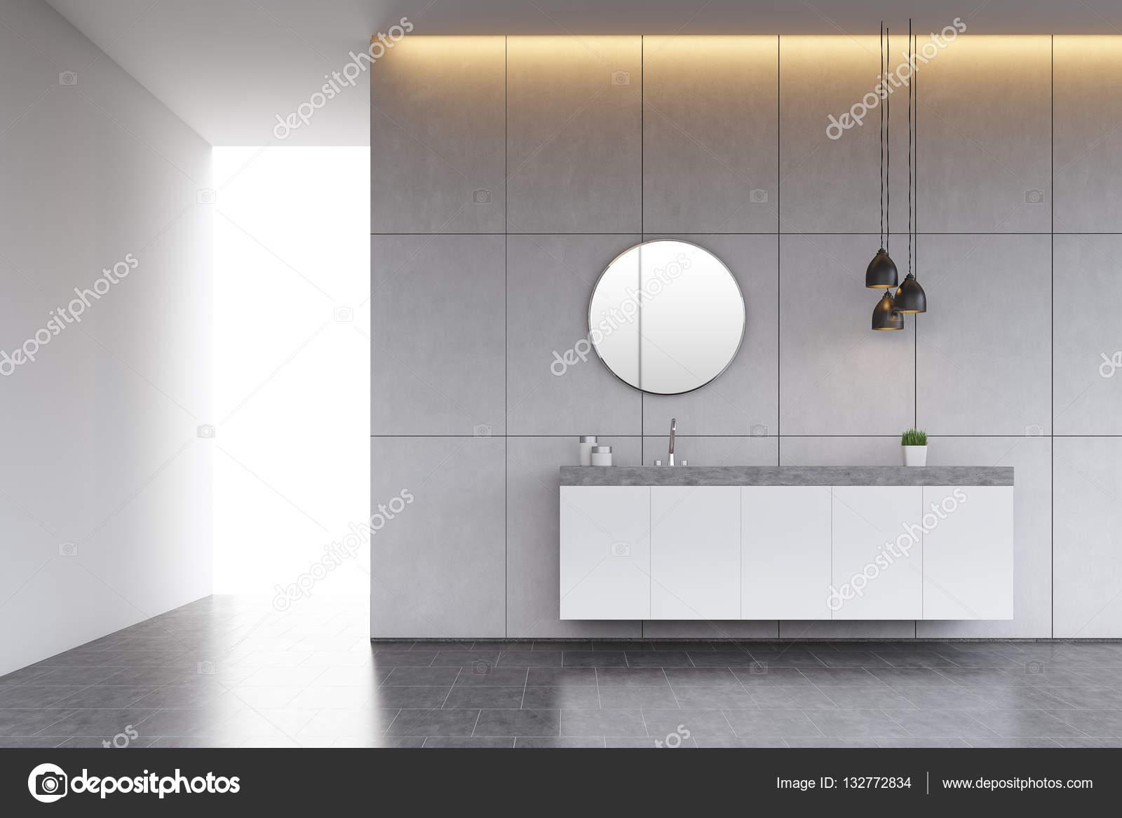 Badkamer wastafel met ronde spiegel op de betegelde muur betonnen