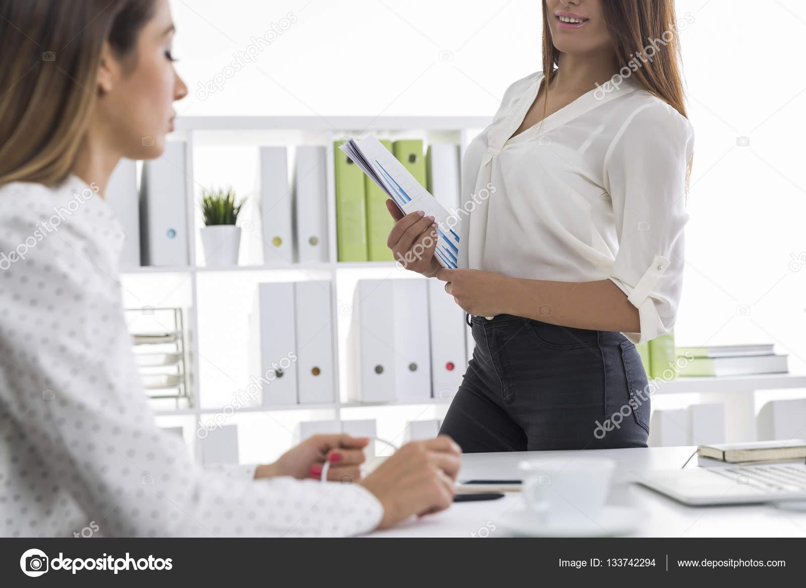 35265072f612 Δύο γυναίκες σε λευκές μπλούζες εργάζονται σε ένα γραφείο– εικόνα αρχείου