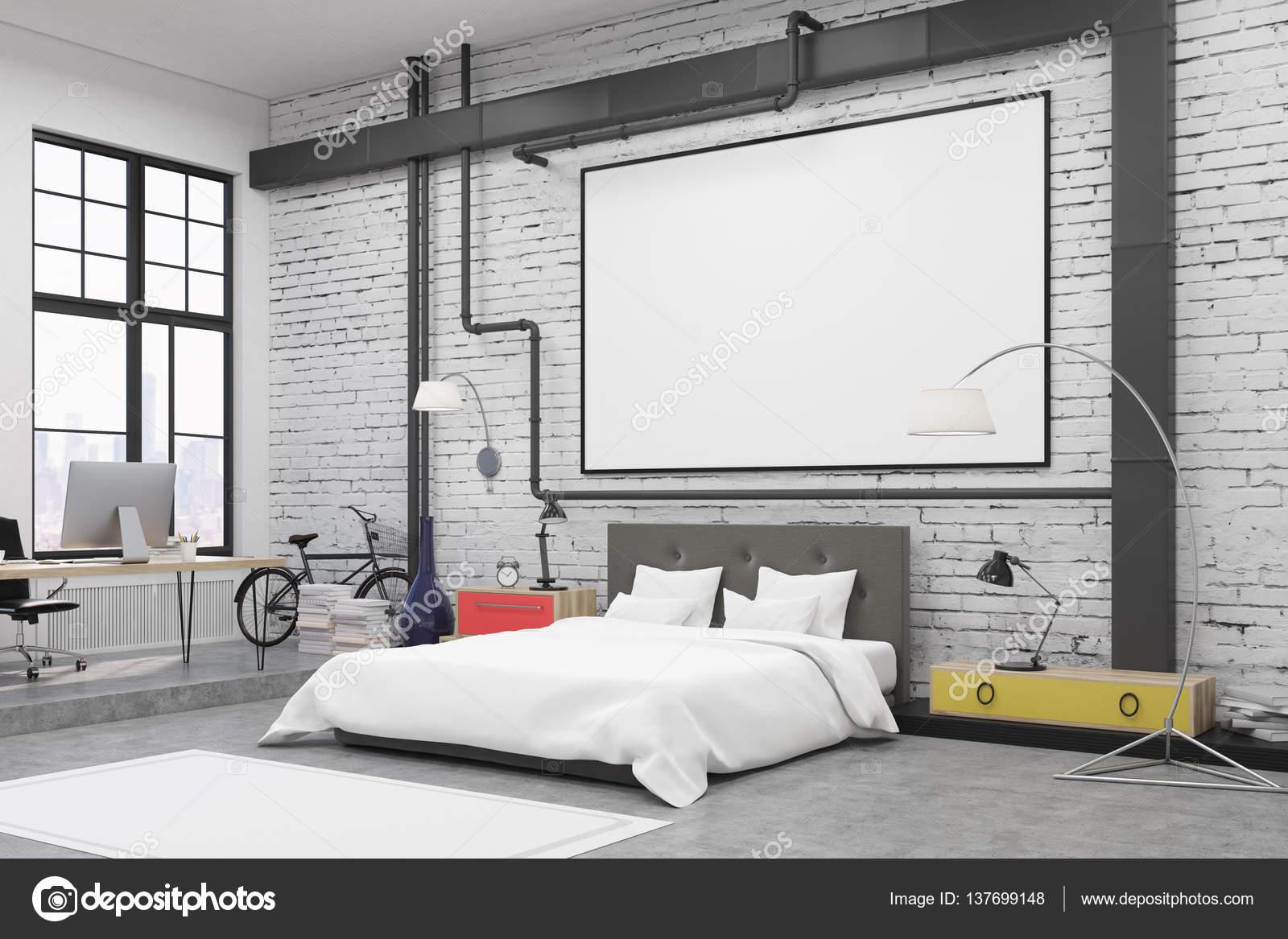 Sidovy av sovrum inredning med vita väggar och en affisch på dem Det finns en stor säng, fåtölj