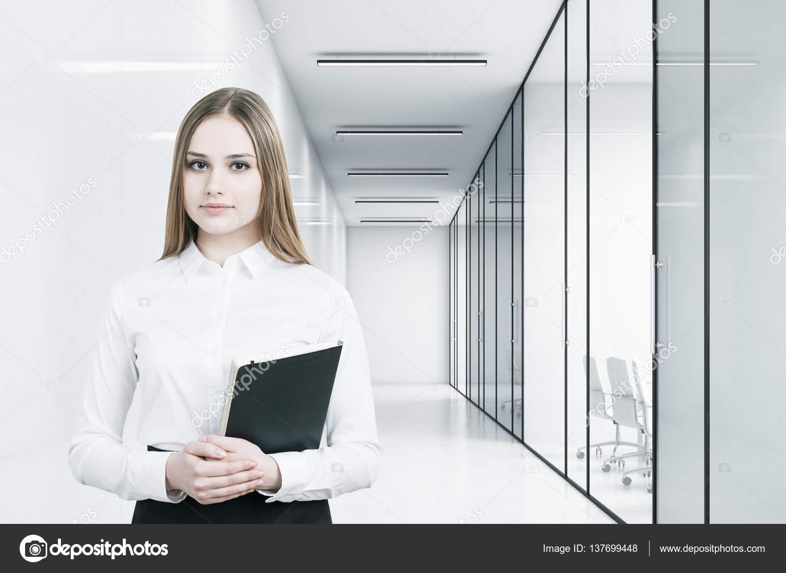 Jeune fille dans un costume de bureau tient un dossier noir et