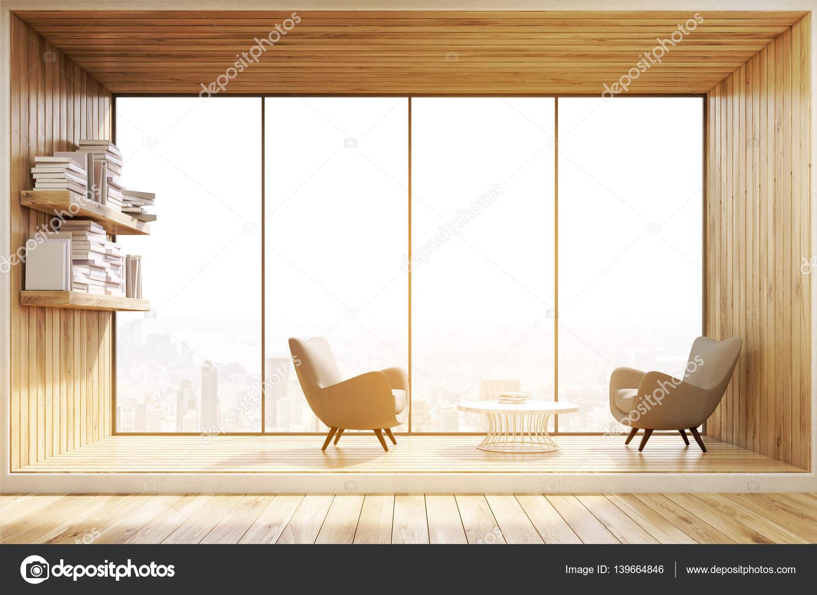 Salón interior con paredes de madera, un ventanal y dos sillones ...