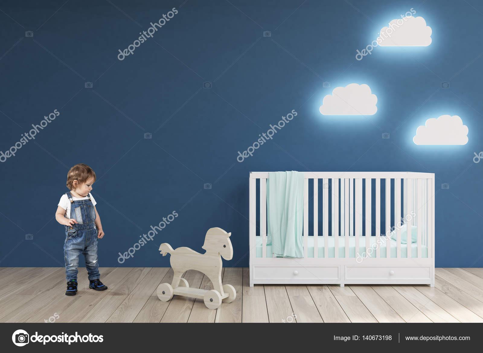 Jongen in een kamer van babys blauwe muren u stockfoto