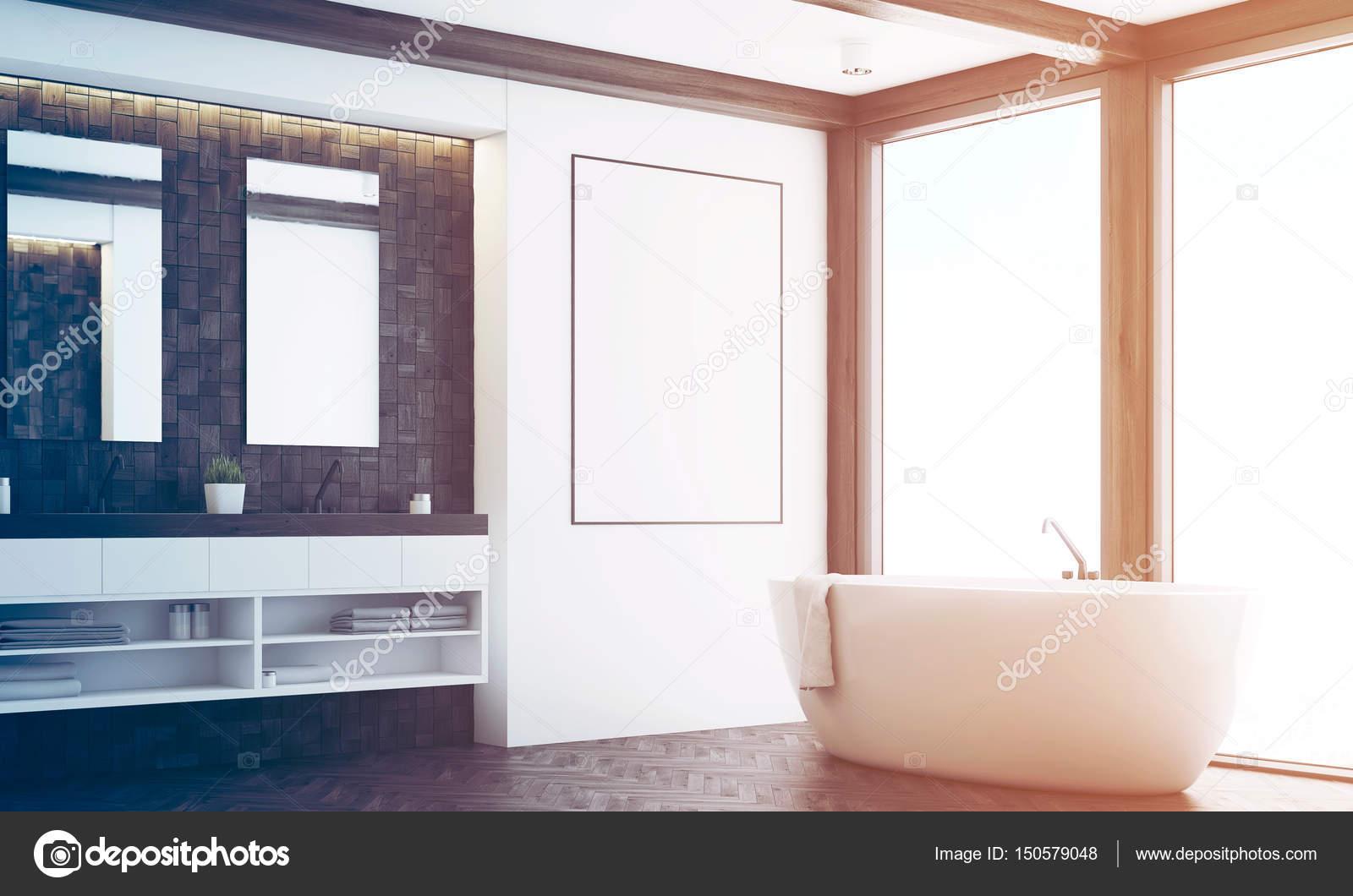 hoek van een badkamer met donkere tegels twee spiegels een dubbele wastafel een grote witte tub en een poster die opknoping in de buurt van het